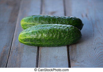 Two cucumbers on wooden background