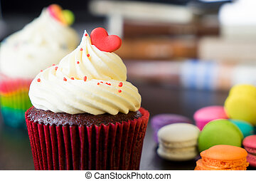 Two cupcake topped with valentines heart with macaron