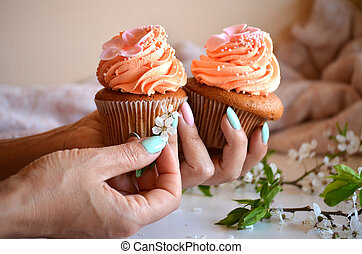 Two cupcakes in the girl's hands closeup