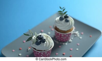 Two cupcakes on a rectangular plate - Two cupcakes with...