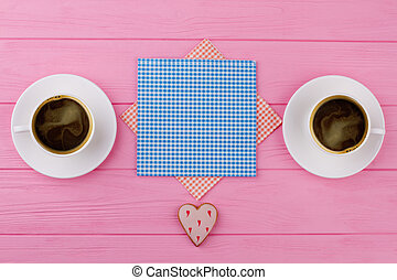 Two cups of black coffee, pink background.