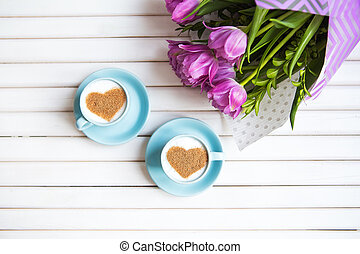 Two cups of cappuccino with a heart shaped symbol and purple tulips on a wooden background