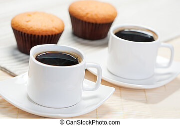 Two cups of coffee and cupcakes