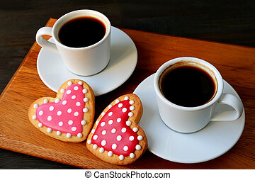 Two cups of coffee and dotted heart shaped royal icing cookies with selective focus
