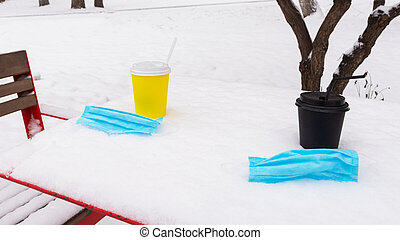 Two cups of coffee and two medical masks on a snow-covered table in the park. Coronavirus concept