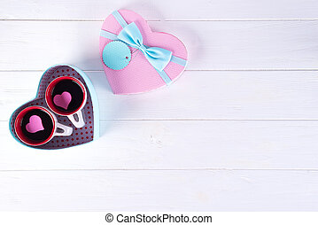 two cups of coffee in a box in the form of a heart on a white background. Valentine's day concept, flat lay with copy space