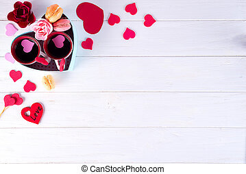 two cups of coffee, macaroons with flowers in a box in the form of a heart on a white background. Valentine's day concept, flat lay with copy space