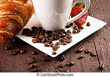 Two cups of coffee with croissants and pieces of cinnamon