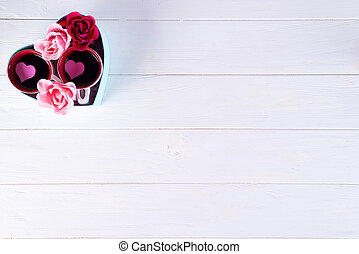 two cups of coffee with flowers in a box in the form of a heart on a white background. Valentine's day concept, flat lay with copy space