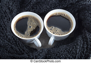 Two cups of coffee wrapped a black wool scarf