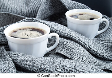 Two cups of hot coffee in the folds of a gray scarf