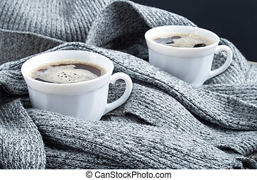 Two cups of hot coffee in the folds of scarf
