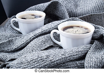 Two cups of hot coffee in the gray scarf