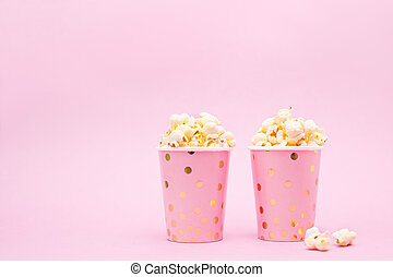 two cups of popcorn on a pink background