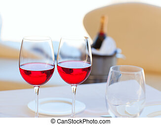 two cups of red wine and bottle in ice bucket - two cups of...