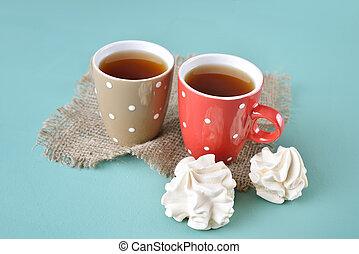 Two cups of tea with meringue cookies
