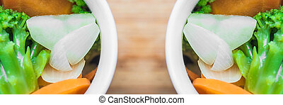 Two cups with fresh vegetables: carrots, broccoli, onions, potatoes. Panoramic shot.