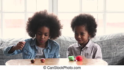 Two cute african children playing with playdough at home