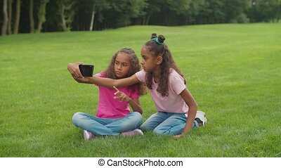 Two lovely elementary age african american sisters sitting on park lawn and having fun, making selfie shot on cellphone, looking with cheerful toothy smiles while enjoying leisure in nature.