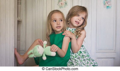 Two cute blonde girls in the dresses hugging each other and smiling