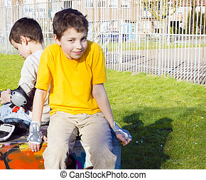 two cute boys in roller-blading protection kits sitting in playground
