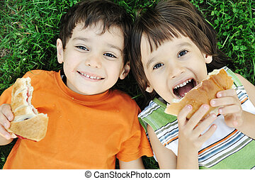 Two cute boys laying on ground in nature and happily eating...