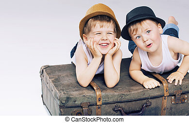 Two cute brothers lying on luggage
