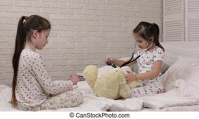 two cute children girls playing doctor with teddy bear at...