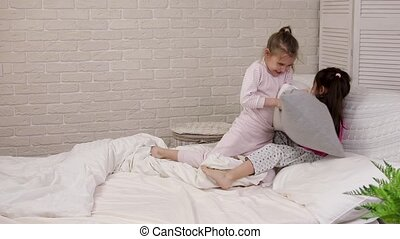 two cute children girls playing in the bedroom. pajama party...