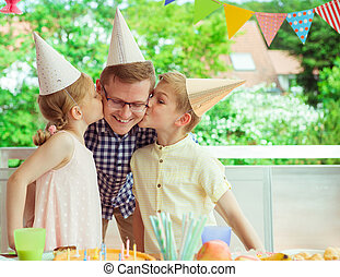 Two cute children kiss their young and happy father at his birthday party on colorful terrace