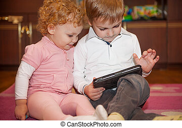 Two cute children playing with tablet