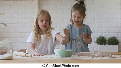 Two cute funny children girls sisters playing with flour having fun cooking together in kitchen, happy preschool kids siblings help prepare dough for cookie with rolling pin learn bake pastry at home