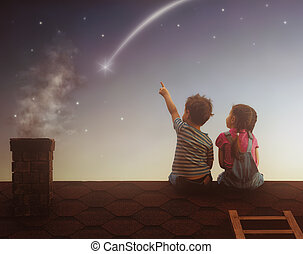 Boy and girl make a wish - Two cute children sit on the roof...