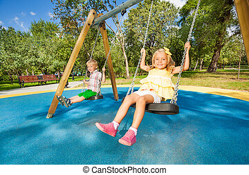 Two cute children swinging on playground