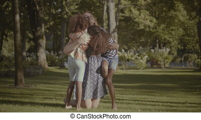 Two cute daughters kissing their mother in nature