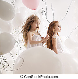Two cute girls among the balloons