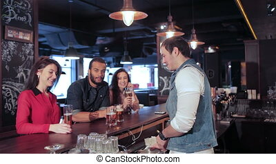 Two cute girls and a guy relaxing in a bar