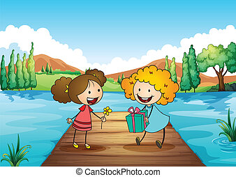 Two cute girls exchanging gifts at the river