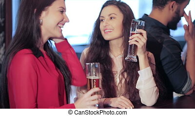 Two cute girls girlfriends meet at the bar, smiling and ringing glasses