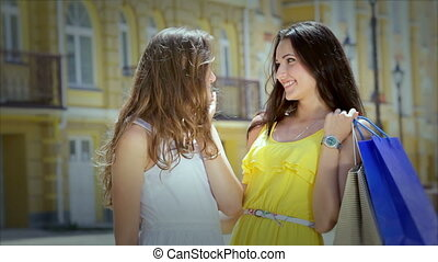 Two cute girls girlfriends smile at each other with fashionable shopping
