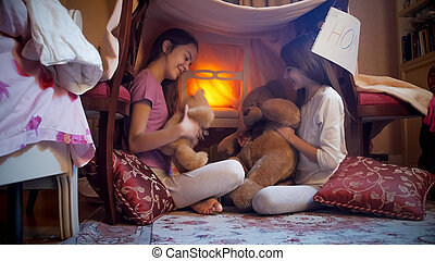 Two cute girls in pajamas playing with teddy bears in bedroom at night