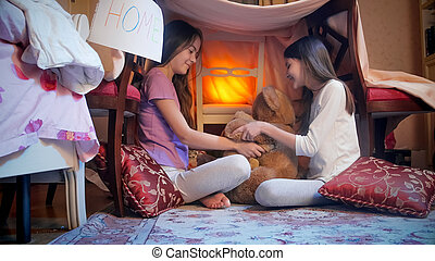 Two cute girls in pajamas playing with teddy bears in selfmade tent at night