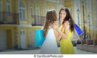 Two cute girls meet while shopping, a friendly hug and posing