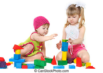 two cute girls playing with building blocks over white