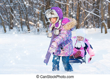 Cute girl pulling sister on a sled through the snow