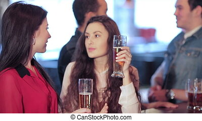 Two cute girls standing at the bar are talking and smiling at the camera