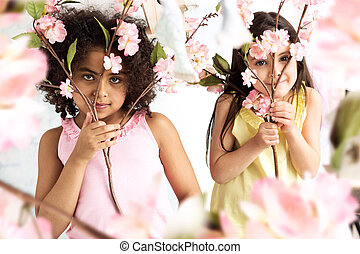 Two cute grils hiding herself behind branches