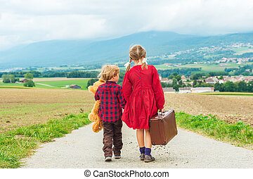 Two cute kids, little girl and her brother, walking down the small road, holding big teddy bear and old brown suitcase