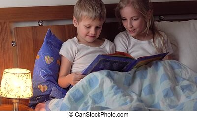 cute kids reading book in bed