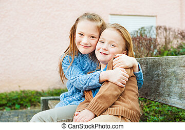 Two cute kids sitting on a bench, big sister hugging little brother
